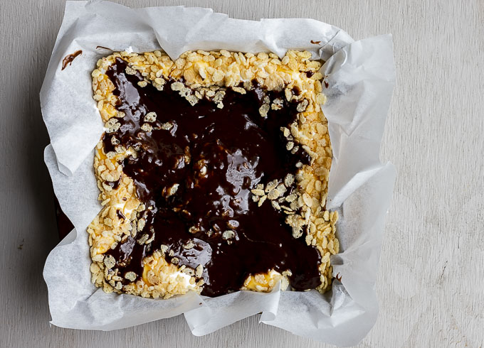 brownies batter on top of rice crispies in a pan