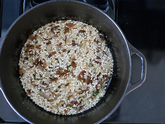 rice and bacon with liquid in a pot