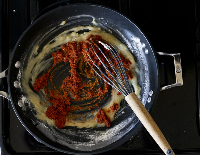 red paste added to roux in a skillet