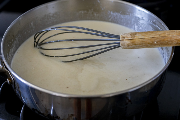creamy white liquid in a skillet with a whisk