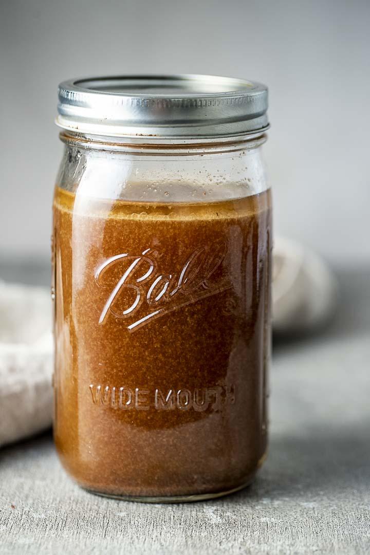 glass jar of brown liquid with a metal lid