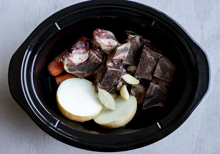 bones, onions and carrots in a slow cooker