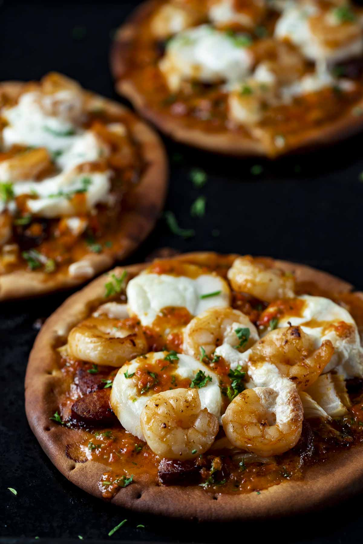 pita bread pizza topped with shrimp, sausage and cheese