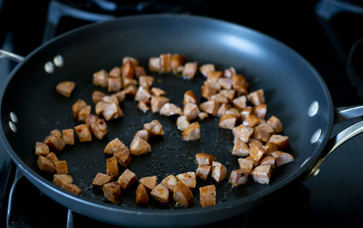 diced sausage frying in a skillet