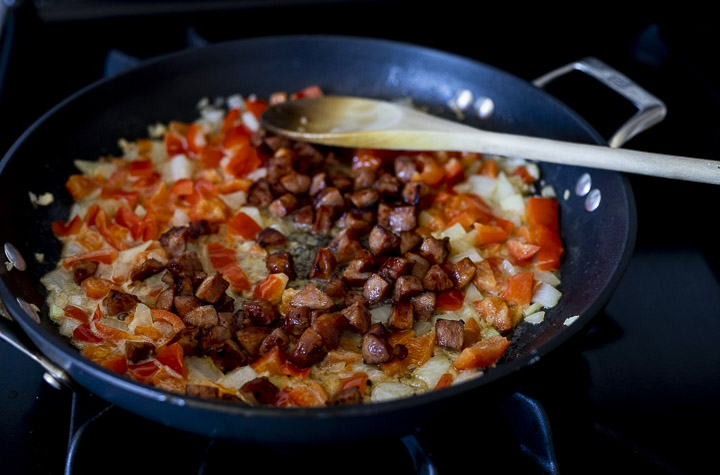 diced onions, red peppers and sausage in a skillet