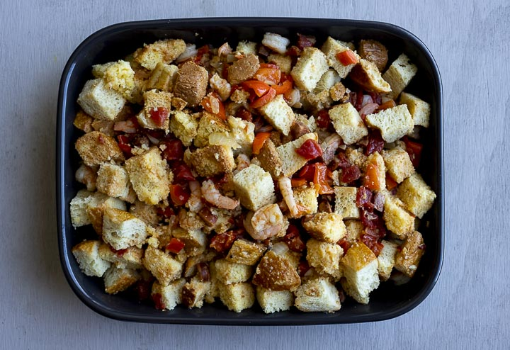 uncooked stuffing with red peppers and sausage in a baking dish