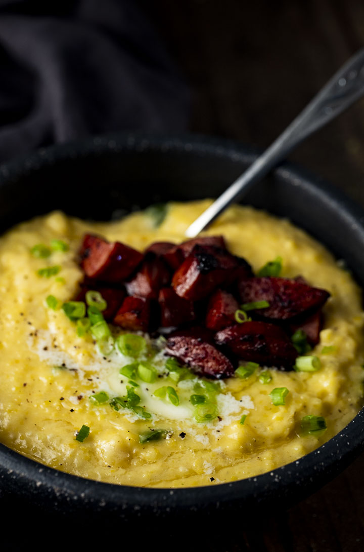a bowl of yellow grits with sausage