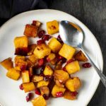 a plate of roasted butternut squash and cranberries with a spoon