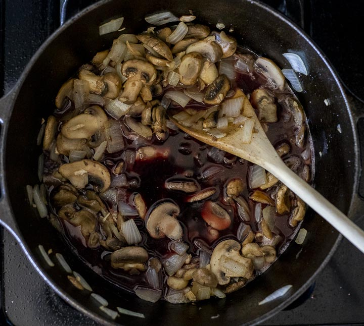 onions and mushrooms cooking with seasonings in a pot