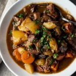 bowl of beef, potatoes and carrots in a brown broth