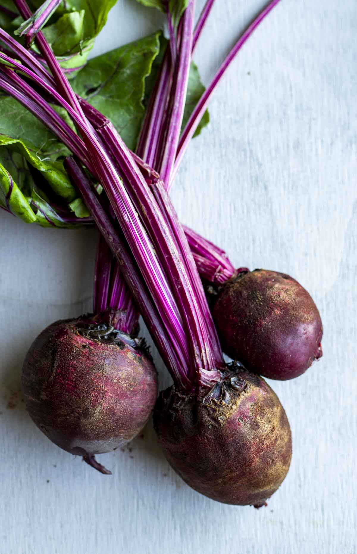 a photo of 3 raw beets with green still attached