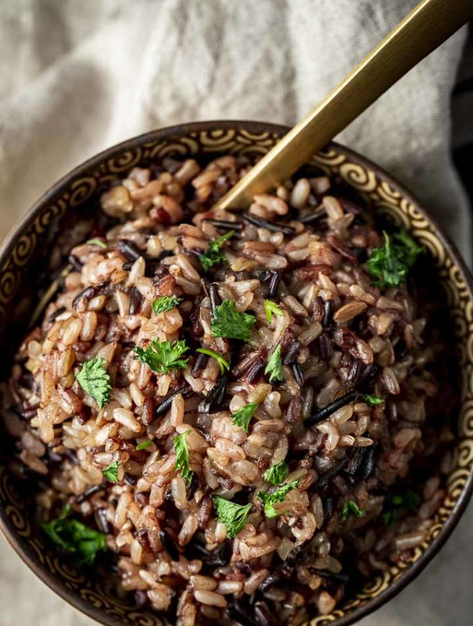 wild rice in a bowl with parsley and a spoon
