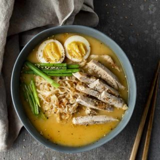 bowl of yellow soup with noodles, turkey and eggs