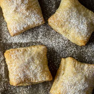 4 pastries covered in powdered sugar on parchment paper
