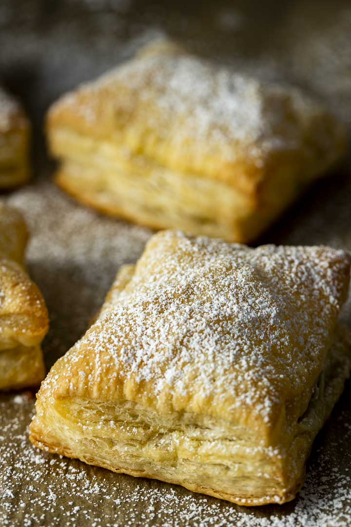 baked puff pastries on a baking sheet sprinkled with sugar