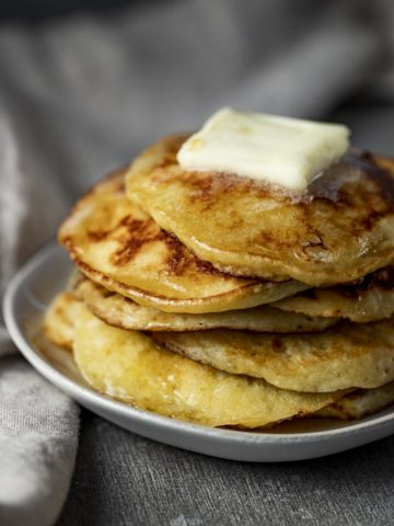 side view of a stack of pancakes drizzled with syrup and butter