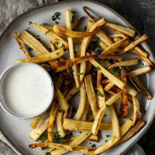a plate of fries with white dipping sauce on the side