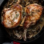 2 cooked pork chops in a skillet with mushrooms
