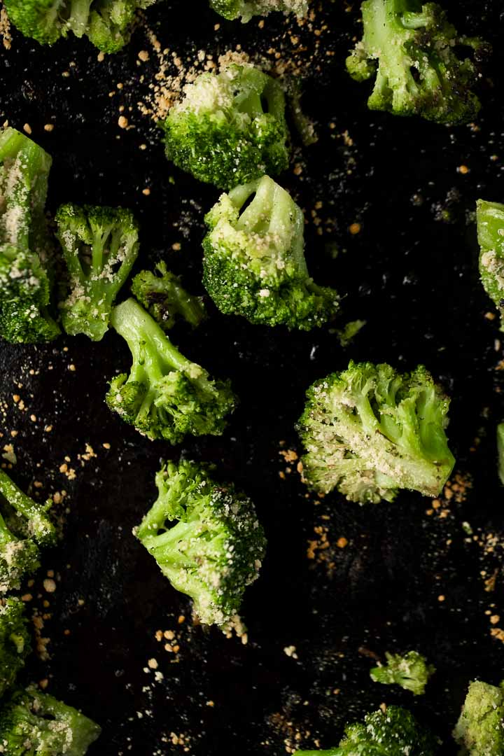 roasted broccoli sprinkled with parmesan cheese on a dark backing sheet