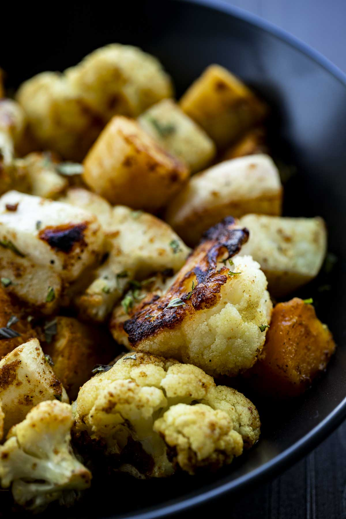 caramelzied piece of roasted cauliflower in a bowl with other roasted vegetables