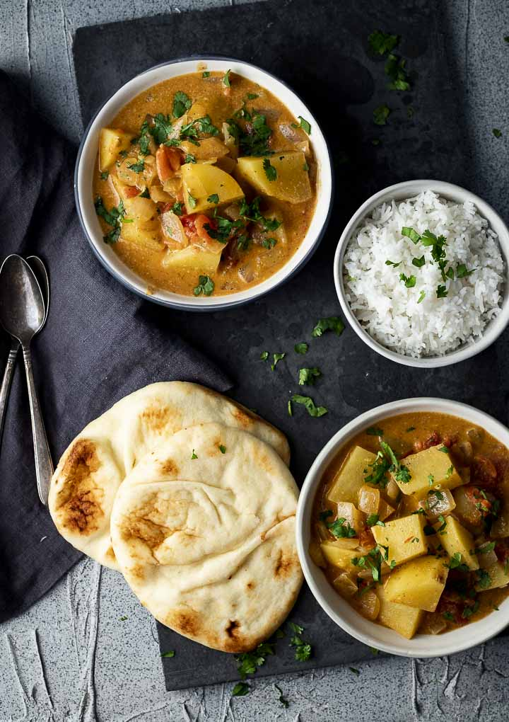 2 bowls of potato curry with a bowl of rice and flatbread (naan) on the side