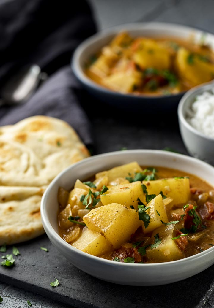 bowl filled with orange colored potato curry garnished with cilantro