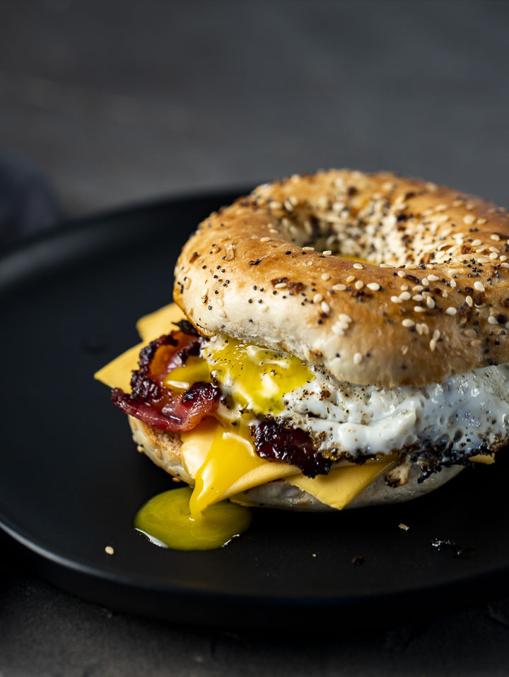 bacon egg and cheese bagel sandwich on a plate