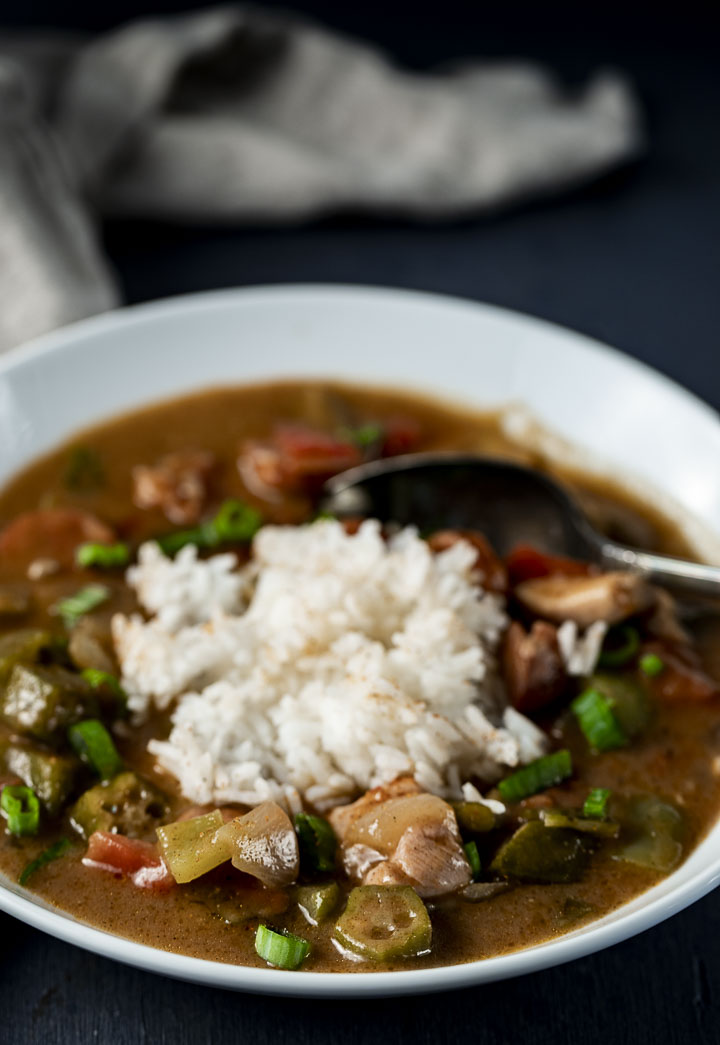 a bowl of gumbo and rice with a spoon