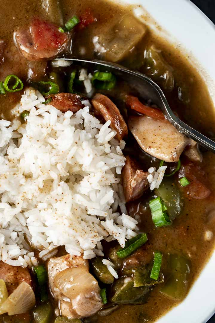 a spoon in a bowl of chicken and sausage gumbo with white rice