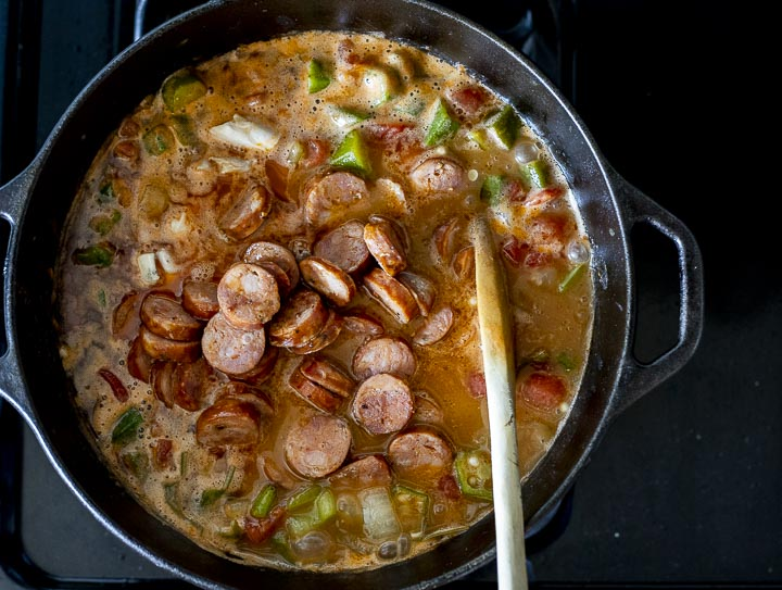 sausage and chicken in a pot with vegetables and broth