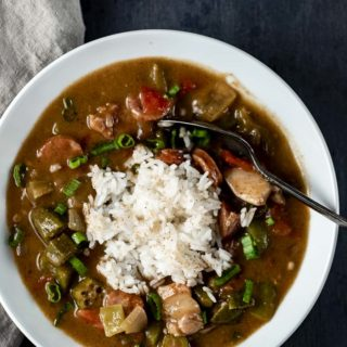 bowl of gumbo with white rice in the middle and a spoon