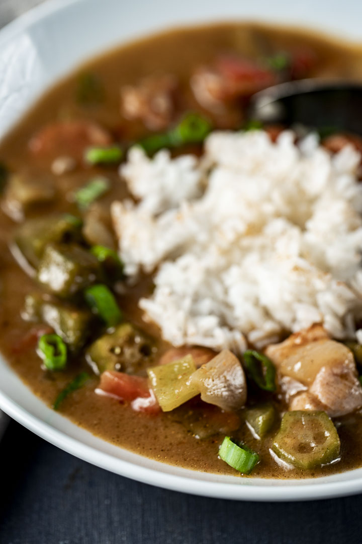chicken and sausage gumbo with okra in a bowl around white rice