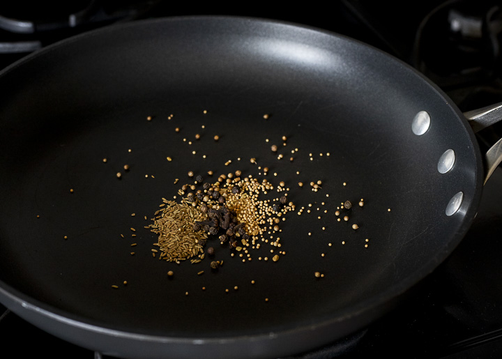 whole spices toasting in a skillet