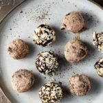 a plate of chocolate truffles rolled in nuts and cocoa powder