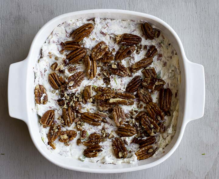 white dip topped with pecans in a baking dish