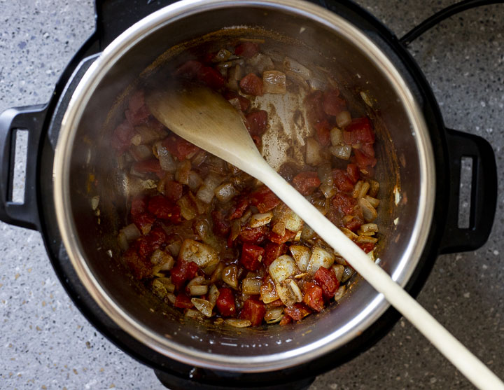 diced onions and tomatoes cooking in a pot