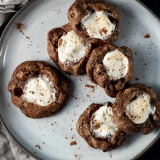 a plate of chocolate cookies with marshmallow in the center