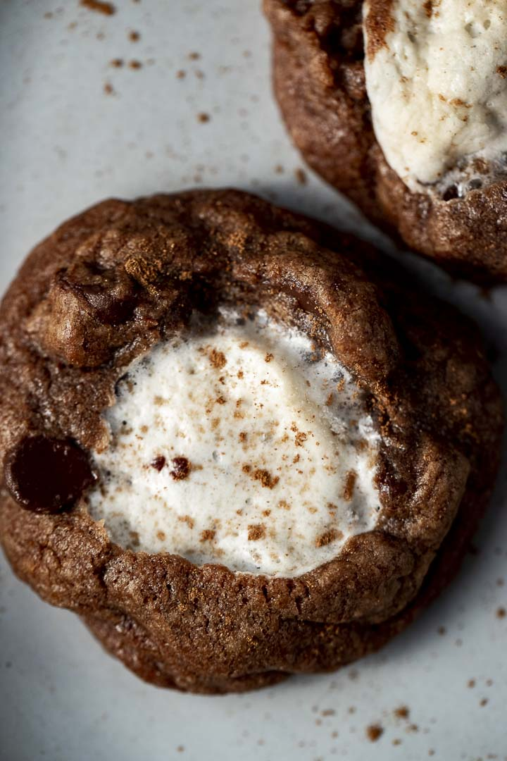 a chocolate cookies with white marshammlow in the middles sprinkled with cinnamon