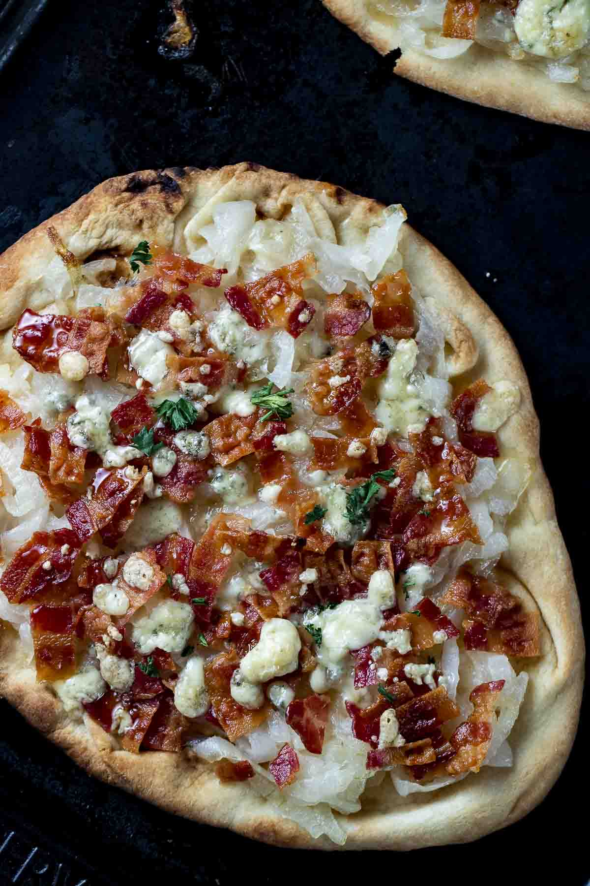pizza with onions, bacon and crumbled cheese on top