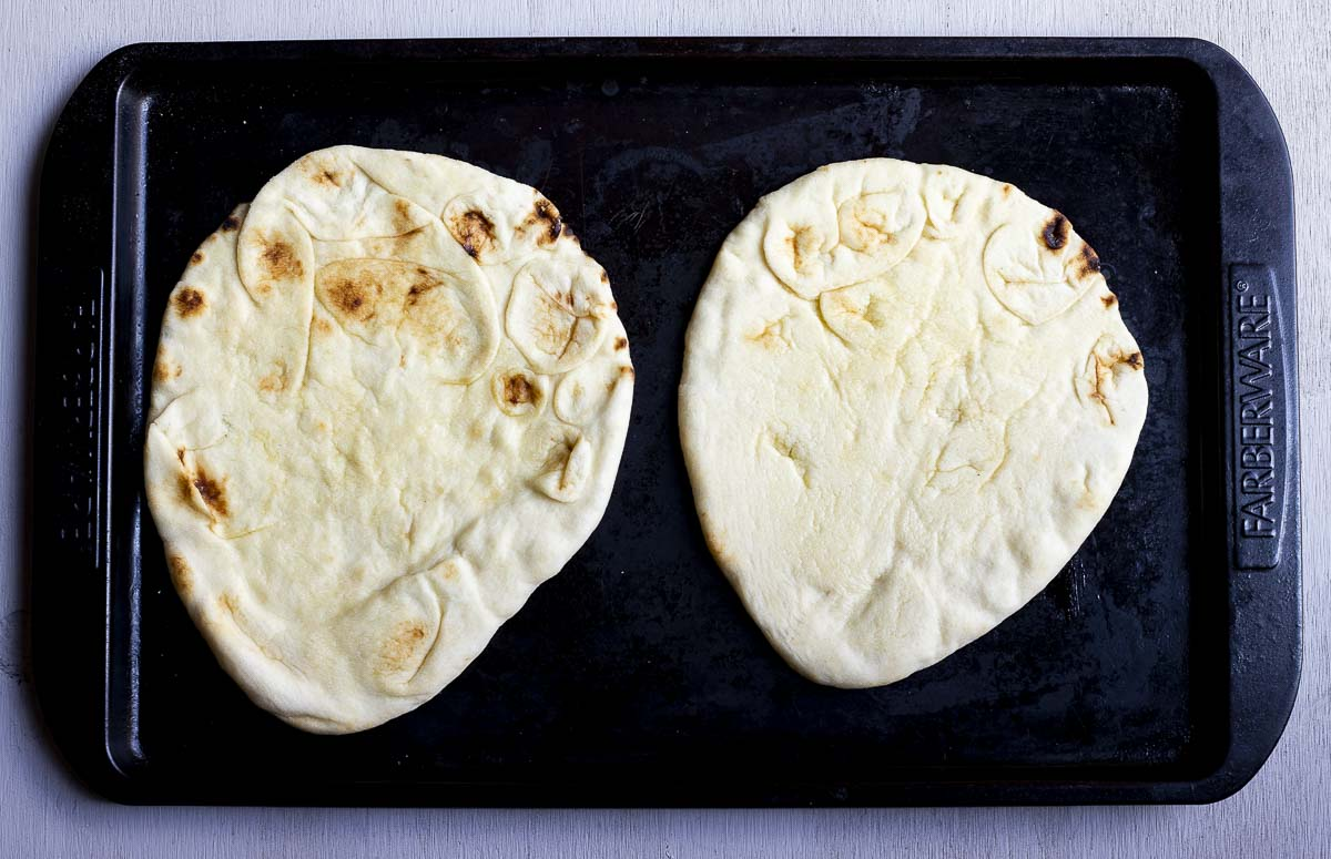 2 pieces of flatbread on a baking sheet