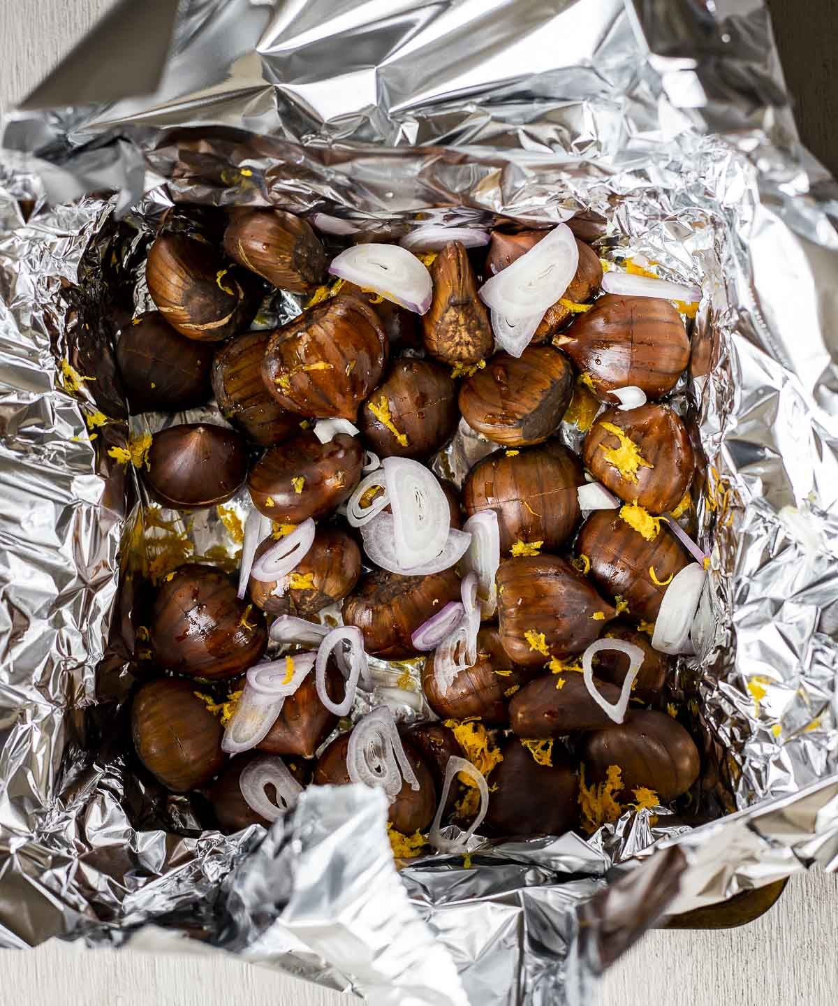 whole chestnuts and shallots in a foil basket