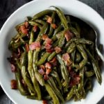a bowl with cooked green beans and bacon with a spoon