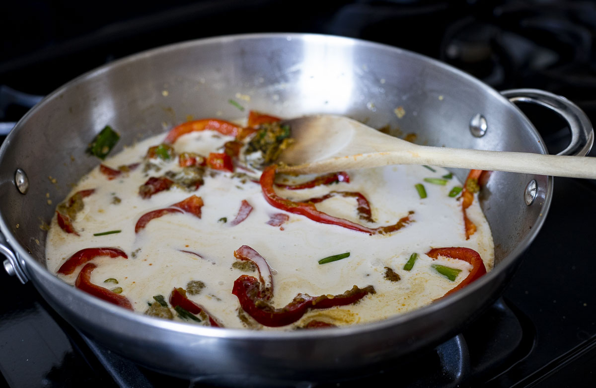 coconut milk in a skillet with red peppers and green onions