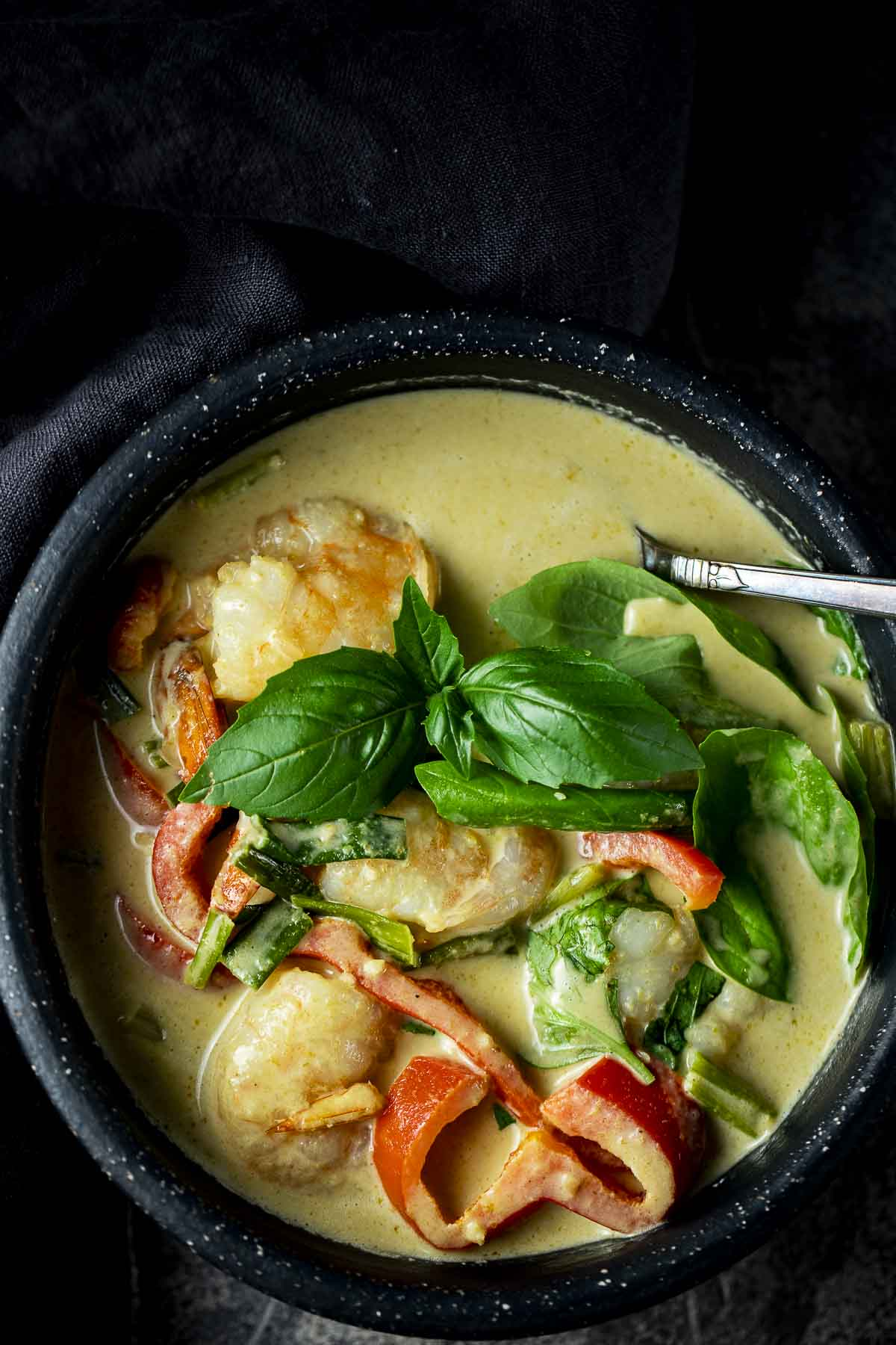 green curry with fresh basil leaves, shrimp and red peppers in a bowl