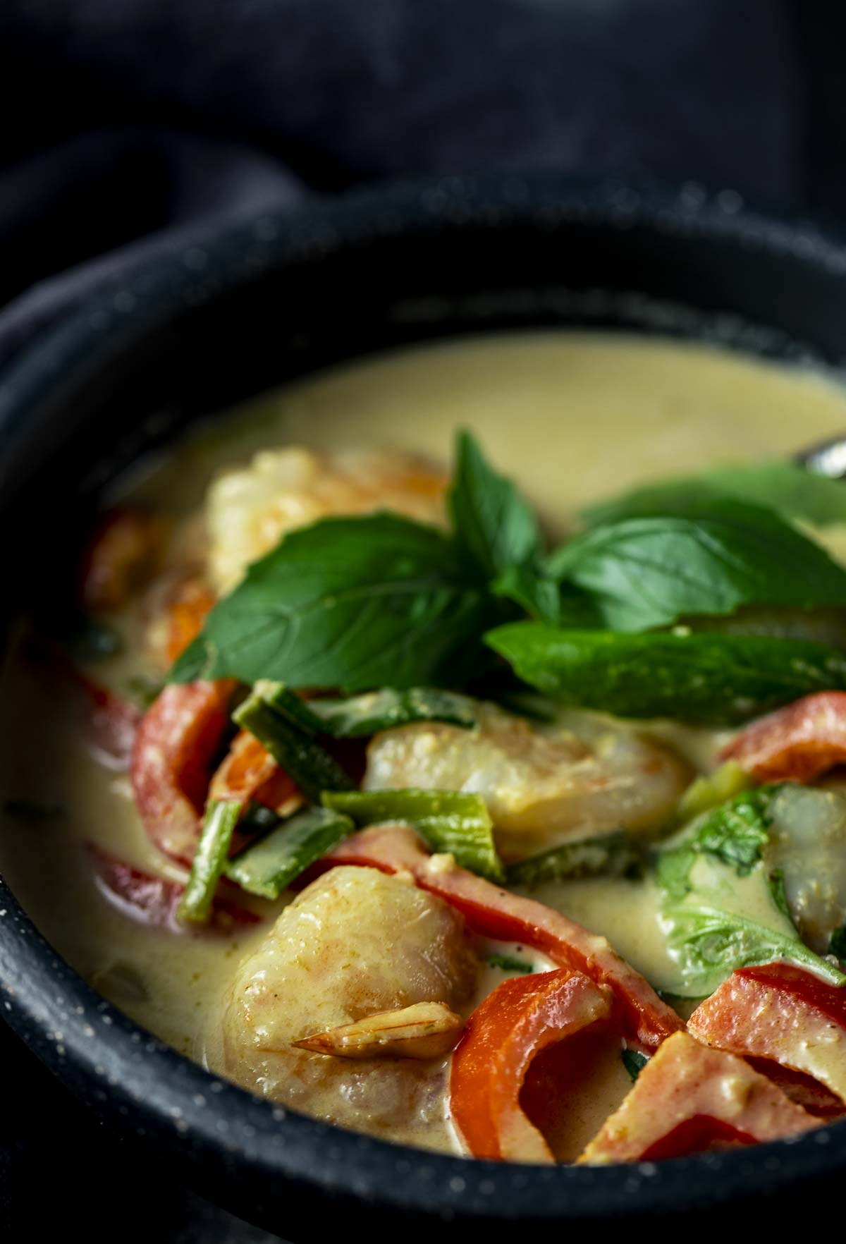shrimp and red peppers in a bowl with creamy green sauce and fresh basil
