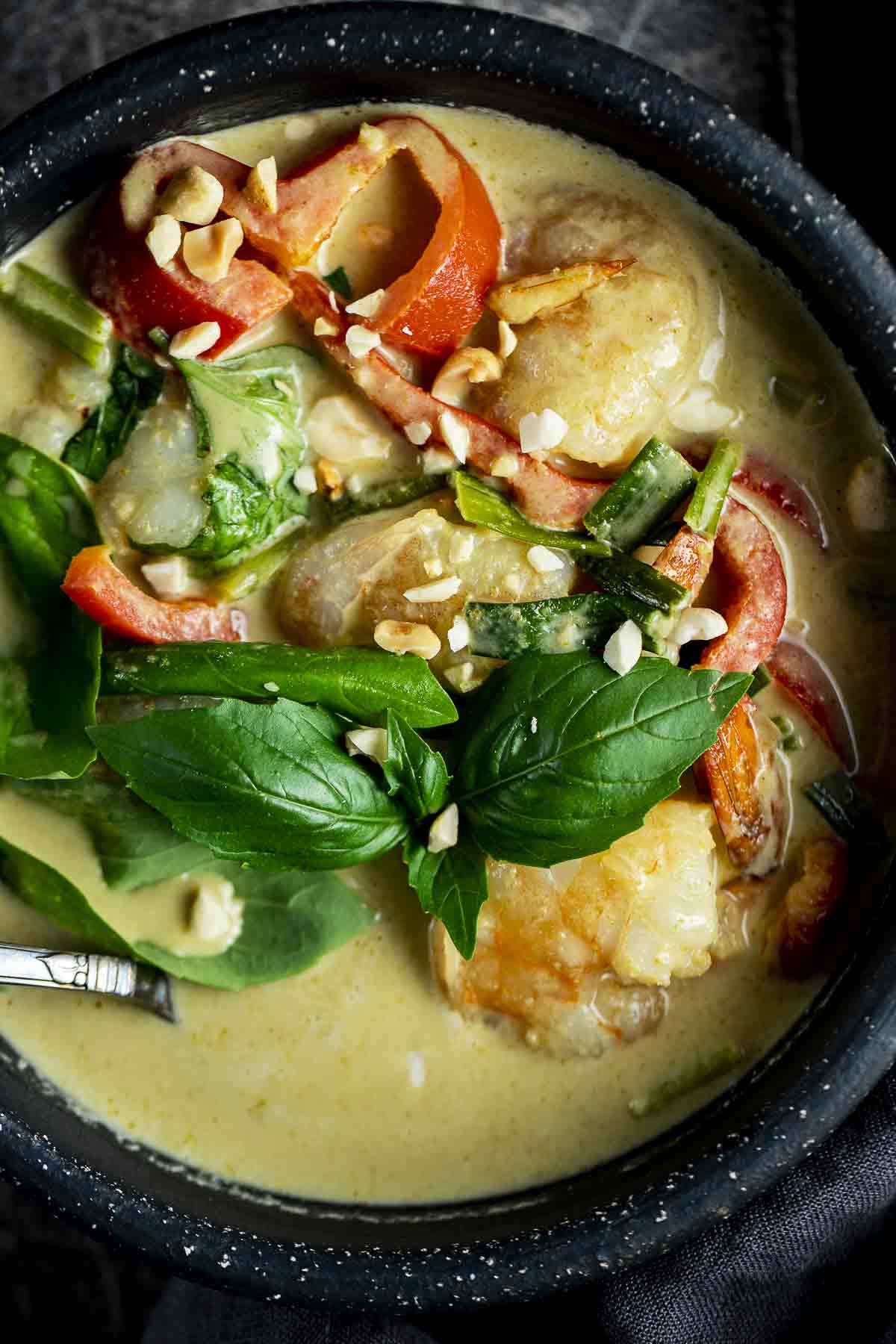 a bowl of green shrimp curry with peppers and fresh basil