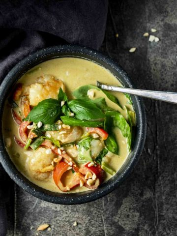 a bowl of curry shrimp and vegetables with a spoon