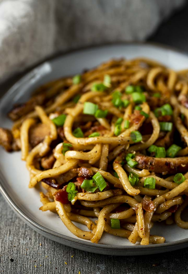stir fried noodles on a plate garnished with green onions