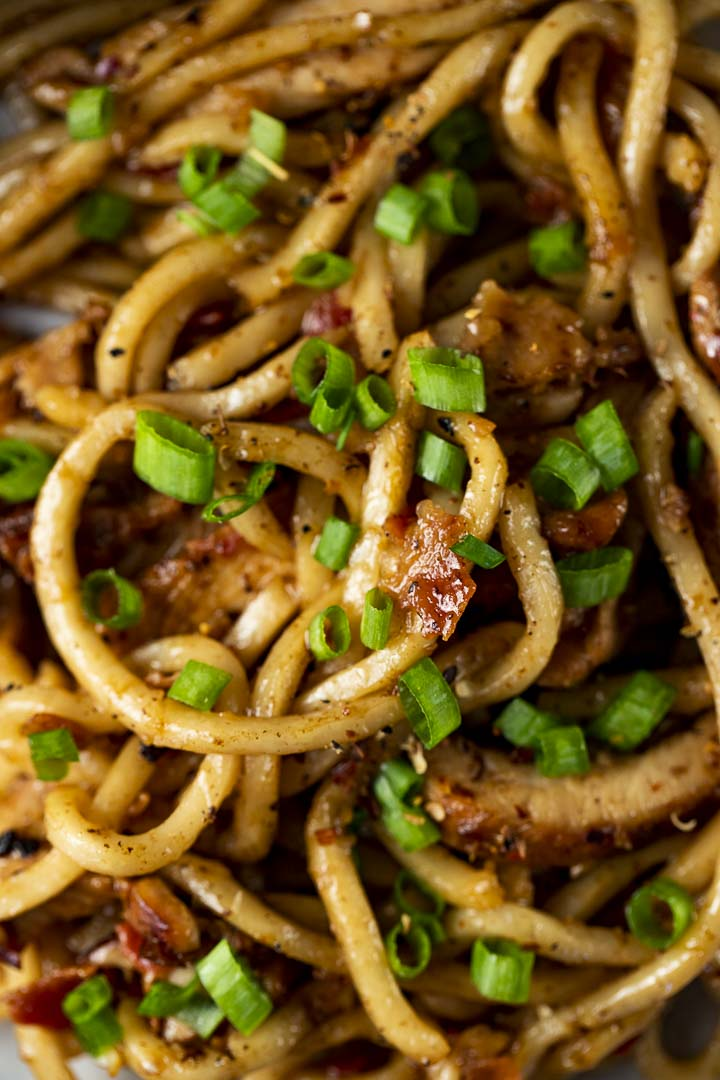 close up photo of noodles stir fried with bacon pieces and green onion