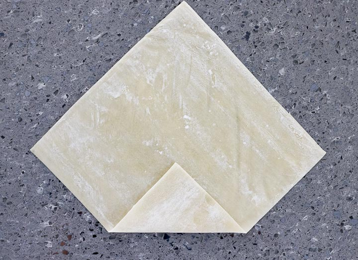 spring roll wrapper on a surface with one corner folded up